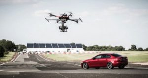 drone flying over a car being driven on a racetrack