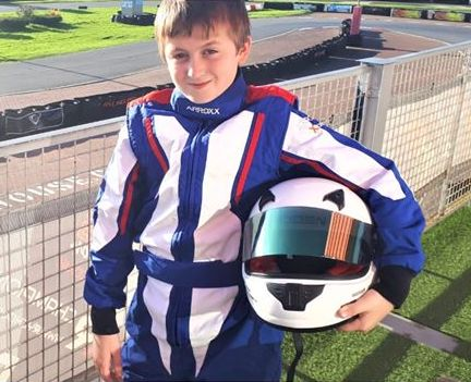 Boy in overalls with helmet at a racetrack