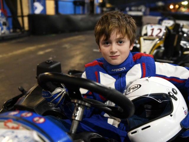 Boy in a stationary race car on a racetrack